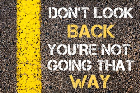 do not: DO NOT LOOK BACK, YOU ARE NOT GOING THAT WAY motivational quote. Yellow paint line on the road against asphalt background Stock Photo
