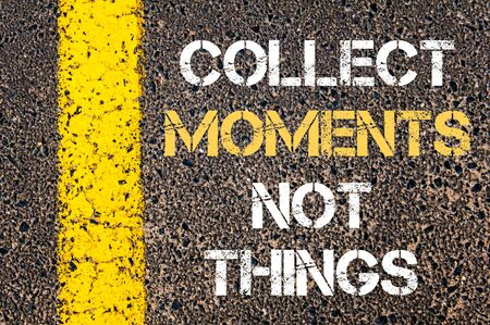 COLLECT MOMENTS NOT THINGS motivational quote. Yellow paint line on the road against asphalt background