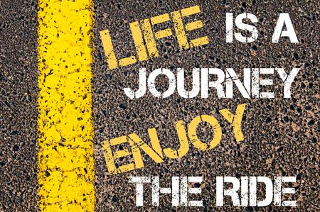 人生は旅をお楽しみください、乗る動機付けの引用。 アスファルトの背景に対して、道路上の黄色塗装ライン