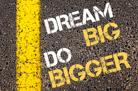 bigger: DREAM BIG DO BIGGER motivational quote. Yellow paint line on the road against asphalt background