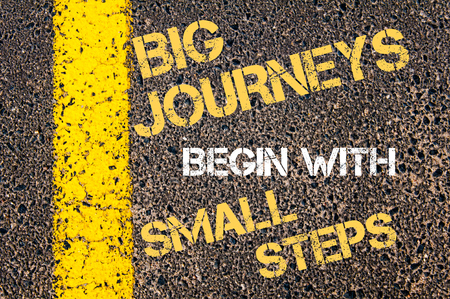 incominciare: GRANDI VIAGGI Inizia con PICCOLI PASSI citazione motivazionale. Vernice linea gialla sulla strada contro sfondo asfalto