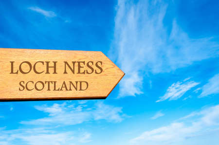 loch ness: Wooden arrow sign pointing destination LOCH NESS, SCOTLAND against clear blue sky with copy space available. Travel destination conceptual image Stock Photo