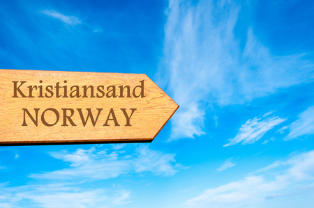 kristiansand: Wooden arrow sign pointing destination KRISTIANSAND, NORWAY against clear blue sky with copy space available. Travel destination conceptual image