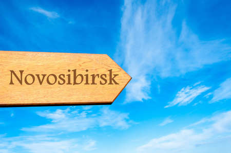 novosibirsk: Wooden arrow sign pointing destination NOVOSIBIRSK, RUSSIA against clear blue sky with copy space available. Travel destination conceptual image