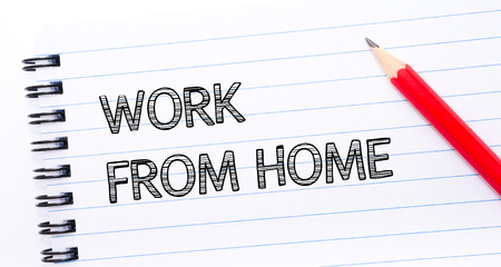 work from home: WORK FROM HOME  written on notebook page, red pencil on the right. Concept image Stock Photo