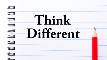 think different: Think Different Text written on notebook page, red pencil on the right Stock Photo