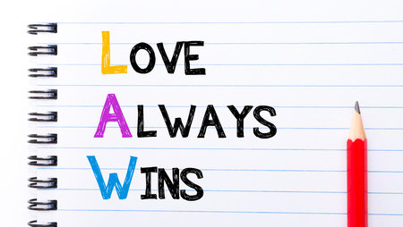 wins: LAW as Love Always Wins Text written on notebook page, red pencil on the right Stock Photo