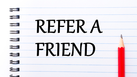 refer: Refer a Friend Text written on notebook page, red pencil on the right Stock Photo