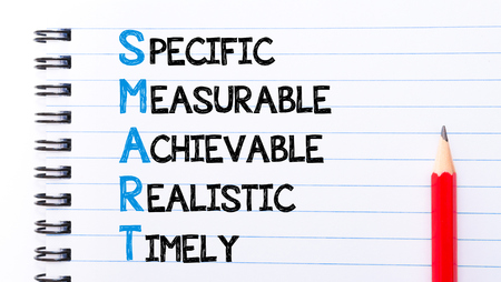 specific: SMART as Specific, Measurable, Achievable, Realistic, Timely Text written on notebook page, red pencil on the right Stock Photo