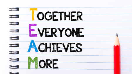 achieves: TEAM as Together Everyone Achieves More Text written on notebook page, red pencil on the right Stock Photo