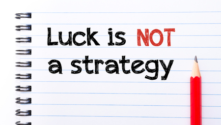 Luck is Not a Strategy Text written on notebook page, red pencil on the right