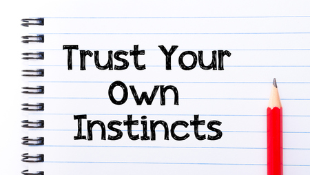 instincts: Trust Your Own Instincts Text written on notebook page, red pencil on the right