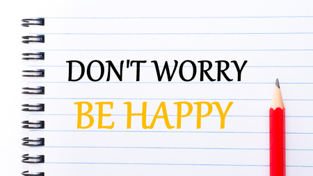 to be or not be: Do Not Worry Be Happy Text written on notebook page, red pencil on the right
