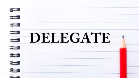 delegar: Delegar Texto escrito en la página del cuaderno, lápiz rojo a la derecha Foto de archivo