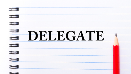 delegate: Delegate Text written on notebook page, red pencil on the right