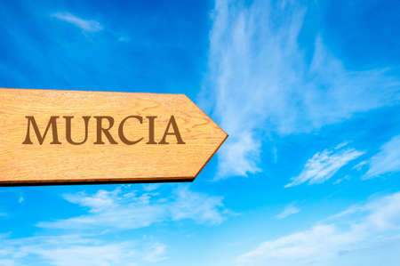 murcia: Wooden arrow sign pointing destination MURCIA, SPAIN against clear blue sky with copy space available Stock Photo