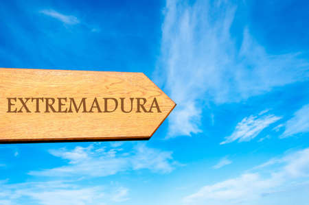extremadura: Wooden arrow sign pointing destination EXTREMADURA, SPAIN against clear blue sky with copy space available
