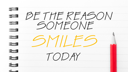 someone: Be The Reason Someone Smiles Today Text written on notebook page, red pencil on the right Stock Photo