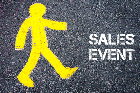 sales event: Yellow pedestrian figure on the road walking towards SALES EVENT. Conceptual image with Text message over asphalt background. Stock Photo