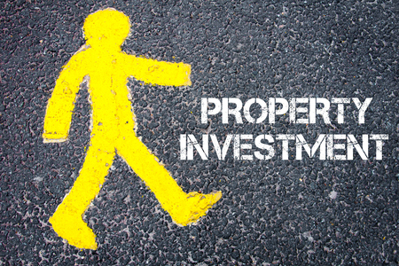 property investment: Yellow pedestrian figure on the road walking towards PROPERTY INVESTMENT. Conceptual image with Text message over asphalt background. Stock Photo