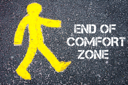 walking zone: Yellow pedestrian figure on the road walking towards End Of Comfort Zone. Conceptual image with Text message over asphalt background. Stock Photo
