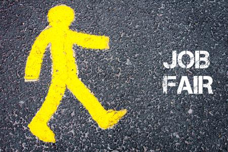 Gele voetganger figuur op de weg lopen naar JOB FAIR. Conceptueel beeld met een SMS-bericht op asfalt achtergrond.