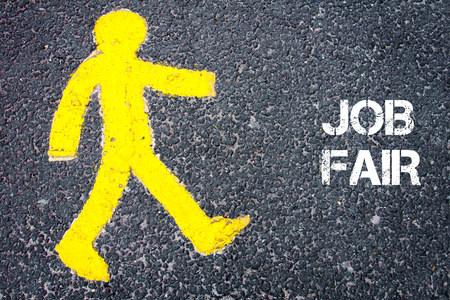 Yellow pedestrian figure on the road walking towards JOB FAIR. Conceptual image with Text message over asphalt background.