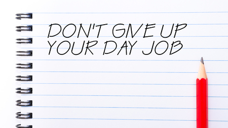 not give: Do Not Give Up Your Day Job Text written on notebook page, red pencil on the right