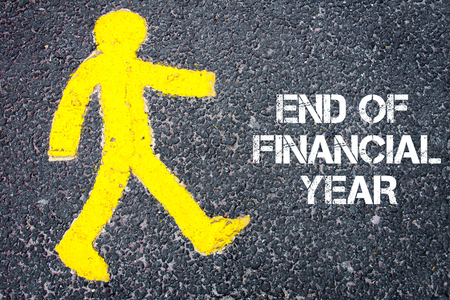 financial figure: Yellow pedestrian figure on the road walking towards END OF FINANCIAL YEAR. Conceptual image with Text message over asphalt background. Stock Photo