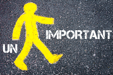 unimportant: Yellow pedestrian figure on the road walking towards IMPORTANT from UNIMPORTANT. Conceptual image with Text message over asphalt background. Stock Photo