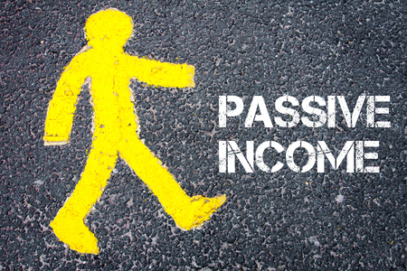 passive income: Yellow pedestrian figure on the road walking towards PASSIVE INCOME. Conceptual image with Text message over asphalt background.