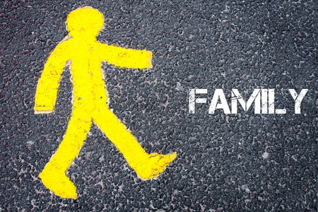 familiy: Yellow pedestrian figure on the road walking towards FAMILIY. Conceptual image with Text message over asphalt background.