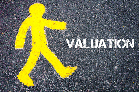 valuation: Yellow pedestrian figure on the road walking towards VALUATION. Conceptual image with Text message over asphalt background. Stock Photo