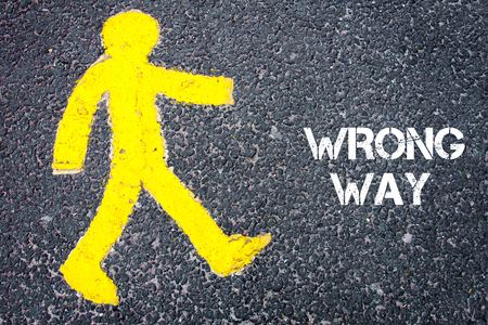 wrong way: Yellow pedestrian figure on the road walking towards WRONG WAY. Conceptual image with Text message over asphalt background. Stock Photo