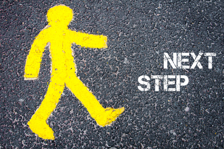 NEXT STEP 향해 걷기 도로에 노란색 보행자 그림. 아스팔트 배경 위에 텍스트 메시지와 함께 개념적 이미지입니다.