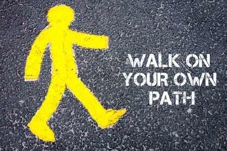 Yellow pedestrian figure on the road walking towards Walk On Your Own Path. Conceptual image with Text message over asphalt background. Stock Photo