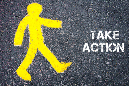 take action: Yellow pedestrian figure on the road walking towards TAKE ACTION. Conceptual image with Text message over asphalt background. Stock Photo