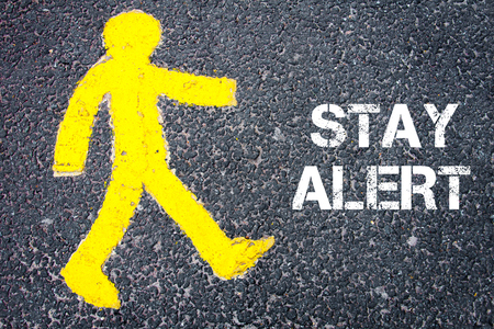 stay alert: Yellow pedestrian figure on the road walking towards STAY ALERT. Conceptual image with Text message over asphalt background.