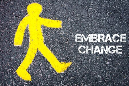 change direction: Yellow pedestrian figure on the road walking towards EMBRACE CHANGE. Conceptual image with Text message over asphalt background.
