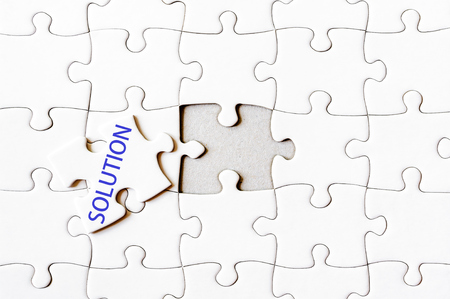 final piece of puzzle: Missing jigsaw puzzle piece with word SOLUTION. Business concept image for completing the final puzzle piece. Stock Photo