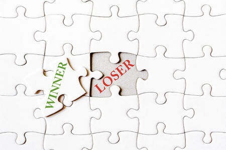 final piece of puzzle: Missing jigsaw puzzle piece with word WINNER, covering text LOSER. Business concept image for completing the final puzzle piece.