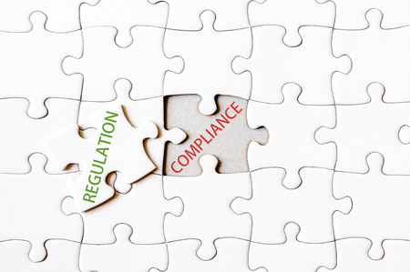 final piece of puzzle: Missing jigsaw puzzle piece with word REGULATION, covering text COMPLIANCE. Business concept image for completing the final puzzle piece.