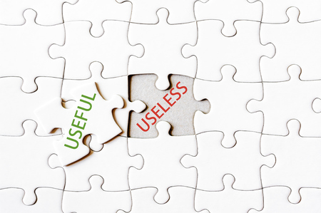 useless: Missing jigsaw puzzle piece with word USEFUL, covering text USELESS. Business concept image for completing the final puzzle piece.
