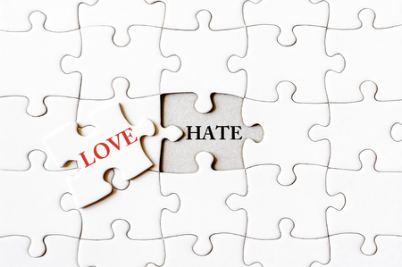 final piece of puzzle: Missing jigsaw puzzle piece with word LOVE, covering text HATE. Business concept image for completing the final puzzle piece.