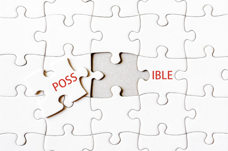 final piece of puzzle: Missing jigsaw puzzle piece completing word POSSIBLE. Business concept image for completing the final puzzle piece. Stock Photo