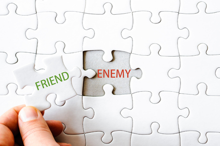 enemy: Hand with missing jigsaw puzzle piece. Word FRIEND, covering  the text ENEMY. Business concept image for completing the final puzzle piece.
