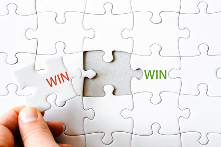 final piece of puzzle: Hand with missing jigsaw puzzle piece completing the wordS WIN WIN. Business concept image for completing the final puzzle piece.