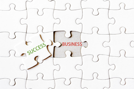 final piece of puzzle: Missing jigsaw puzzle piece with word SUCCESS, covering text BUSINESS. Business concept image for completing the final puzzle piece. Stock Photo