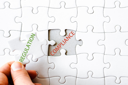 final piece of puzzle: Hand with missing jigsaw puzzle piece. Word REGULATION, covering  text COMPLIANCE. Business concept image for completing the final puzzle piece. Stock Photo