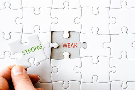 final piece of puzzle: Hand with missing jigsaw puzzle piece. Word STRONG, covering  the text WEAK. Business concept image for completing the final puzzle piece. Stock Photo